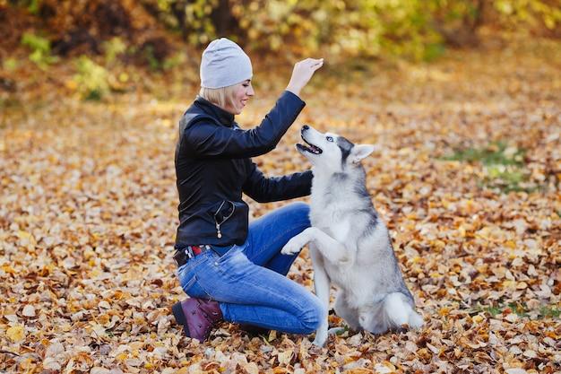 La bella donna gioca con il cane husky nella foresta di autunno