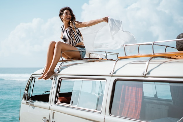 La bella donna gode della natura di viaggio stradale che si siede sul tetto