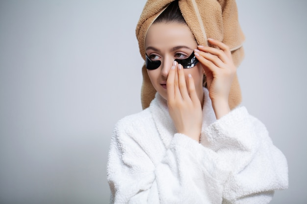 La bella donna in camice bianco applica toppe sugli occhi per la cura della pelle
