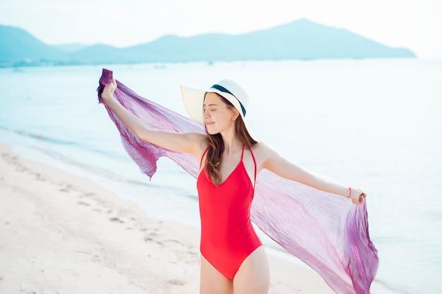 La bella donna in costume da bagno rosso sta rilassandosi sulla spiaggia, concetto dell'estate