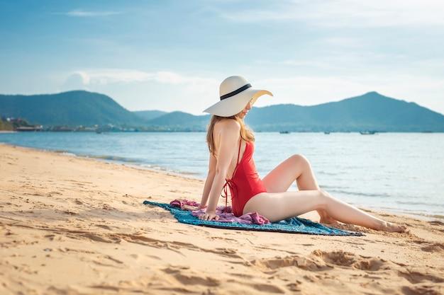 La bella donna in costume da bagno rosso sta sedendosi sulla spiaggia