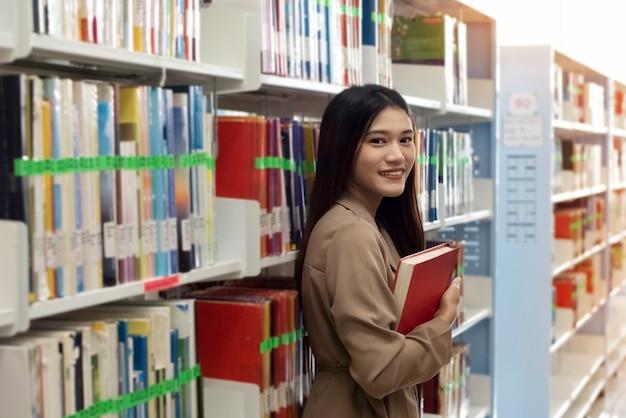 La bella donna in piedi accanto allo scaffale, tenendo in mano il libro con la faccia sorridente, in biblioteca, la luce sfocata intorno