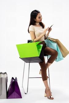 La bella donna in possesso di borse per la spesa in mano, utilizzando il telefono cellulare per lo shopping online