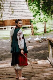 La bella donna in un abito ricamato tradizionale sta camminando a piedi nudi