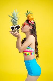 La bella donna in un costume da bagno che tiene un ananas posa sul giallo
