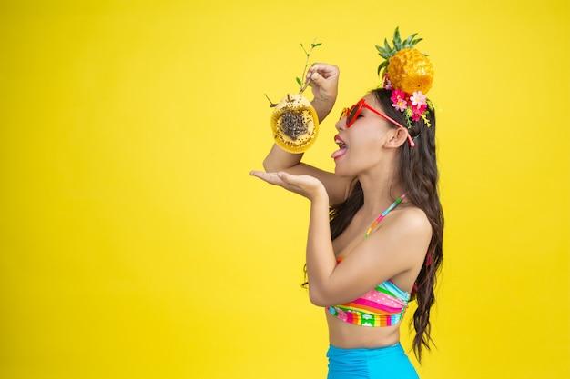 La bella donna in un costume da bagno che trasporta un favo posa sul giallo
