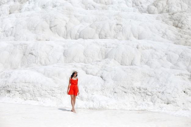 La bella donna in un vestito rosso sta contro le montagne bianche