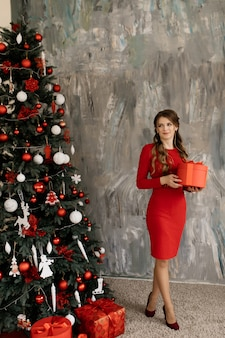 La bella donna in vestito rosso posa prima di albero di natale ricco