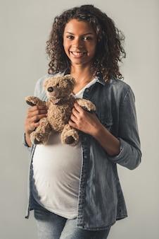 La bella donna incinta di afro sta tenendo un orsacchiotto