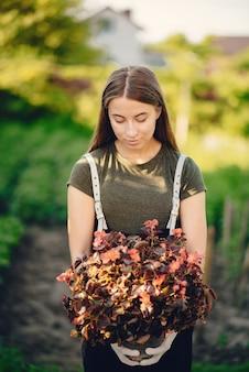 La bella donna lavora in un giardino vicino alla casa