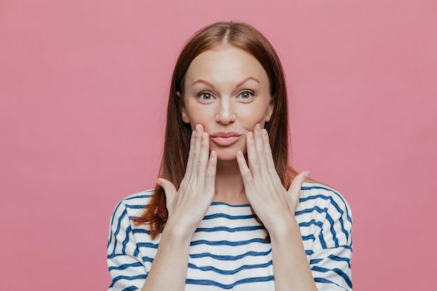 La bella donna lentigginosa tiene le mani vicino alle labbra, ha un trucco minimo, una pelle sana