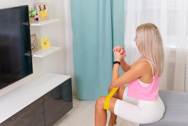 La bella donna nella fabbricazione di vestiti sportivi di modo si esercita con la banda gialla a casa. allenamenti domestici di concetto