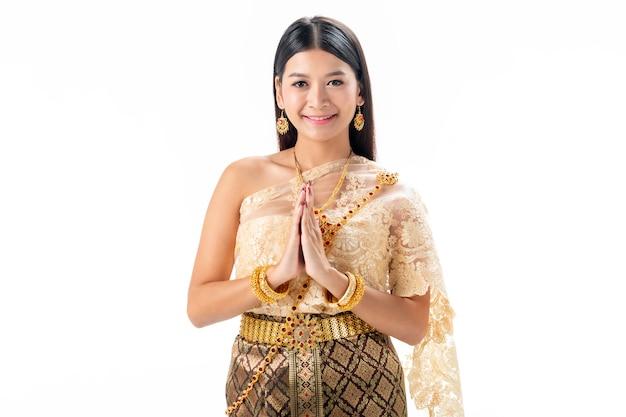 La bella donna paga il rispetto in costume tradizionale nazionale della tailandia. isotate su sfondo bianco.