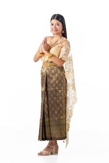 La bella donna paga il rispetto in costume tradizionale nazionale della tailandia.
