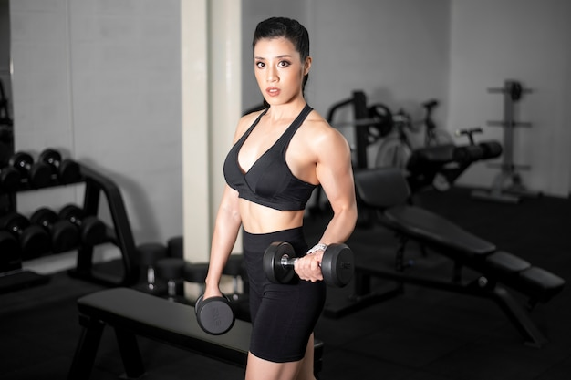 La bella donna perfetta del corpo è allenarsi in palestra