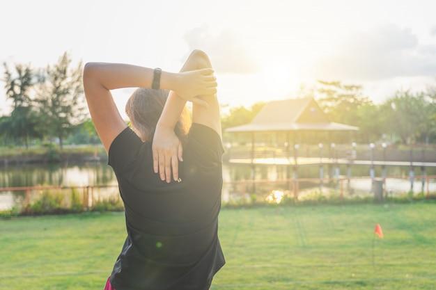 La bella donna rilassa i muscoli dopo l'esercizio appena finito per proteggere i muscoli