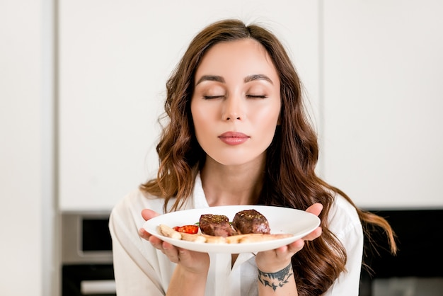 La bella donna sente l'odore della carne appena cucinata sulla cucina