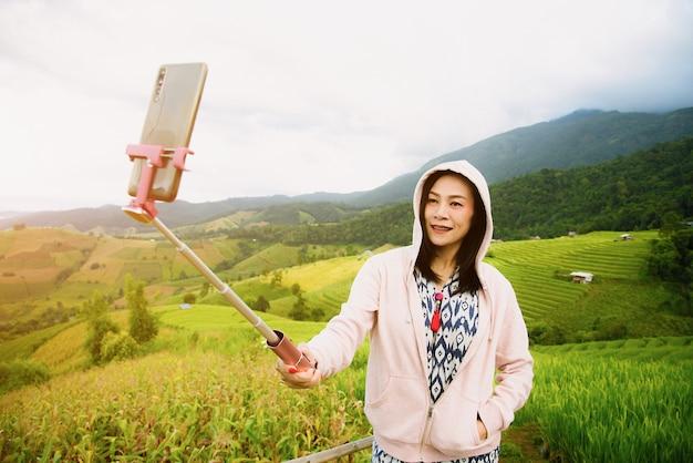 La bella donna si sta fotografando con un telefono cellulare