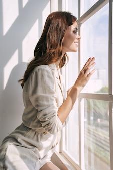 La bella donna sorride e guarda fuori dalla finestra.