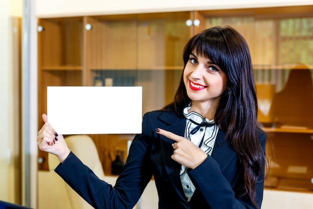 La bella donna sorridente mostra la carta vuota in ufficio