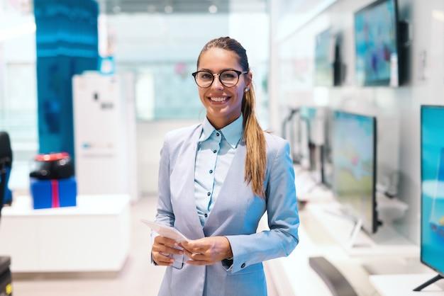 La bella donna sorridente si è vestita in vestito che sta nel deposito di tecnologia