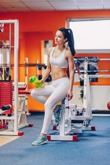 La bella donna sportiva con un corpo perfetto mantiene la bottiglia dell'agitatore in mano in palestra
