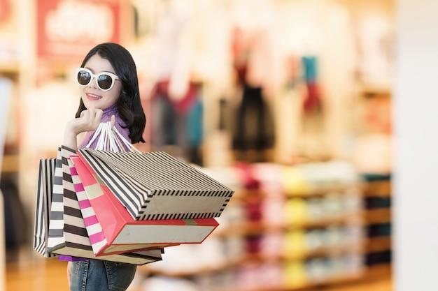 La bella donna sta acquistando nel centro commerciale facendo uso della carta di credito donna che indossa i vetri e che tiene modo del sacchetto della spesa