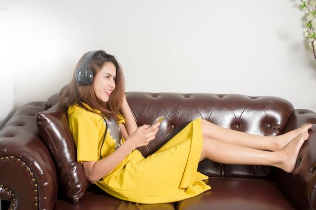 La bella donna sta ascoltando musica nel paese