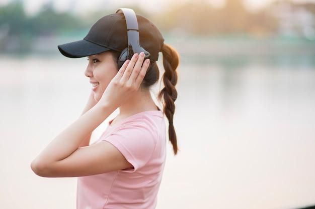 La bella donna sta ascoltando musica nel parco