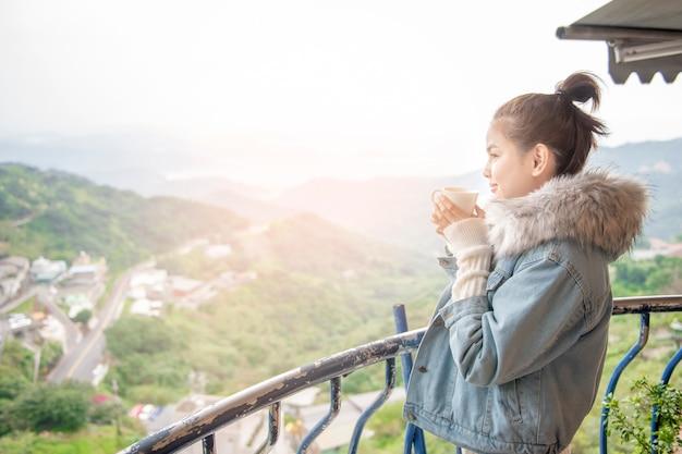 La bella donna sta bevendo il caffè di mattina con il fondo della natura