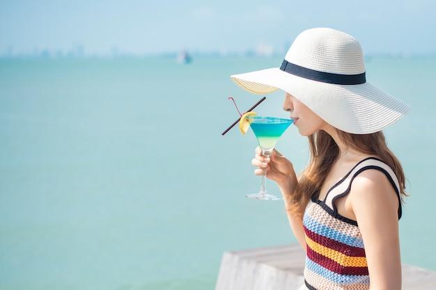 La bella donna sta bevendo la bevanda dell'estate del ghiaccio nella spiaggia, concetto dell'estate