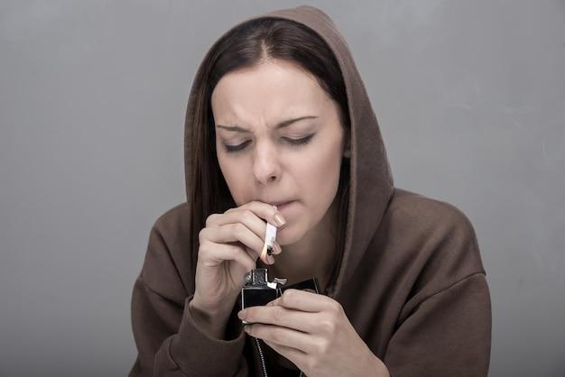 La bella donna sta fumando una sigaretta.