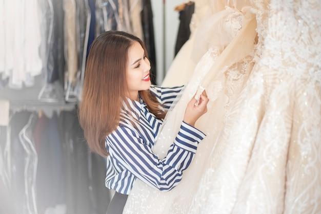 La bella donna sta guardando il vestito da sposa nel negozio di nozze
