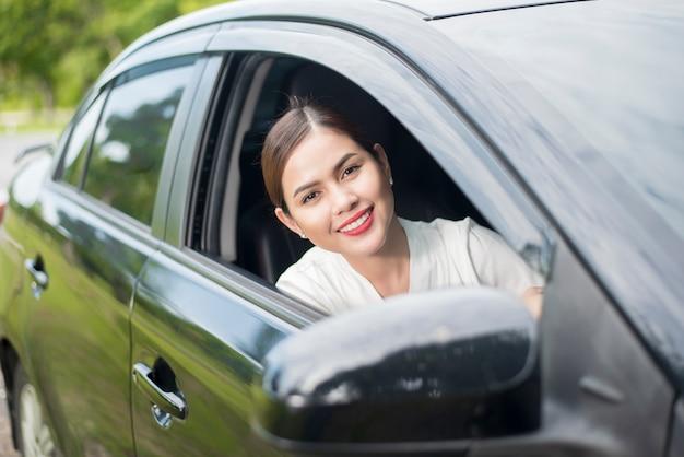La bella donna sta guidando la sua auto