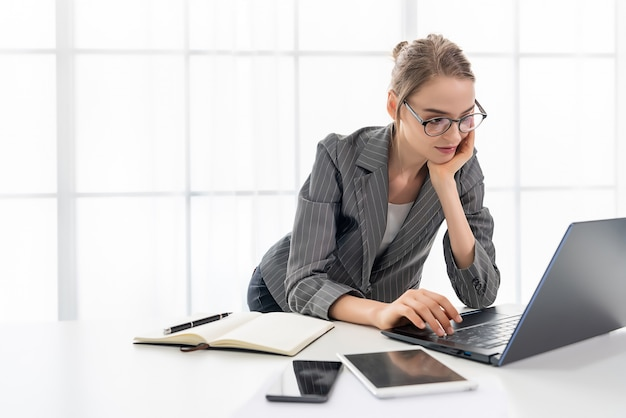 La bella donna sta lavorando a casa con il suo computer portatile. la donna indossa occhiali e abito grigio.