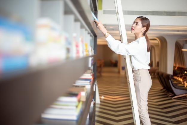La bella donna sta leggendo i libri in biblioteca