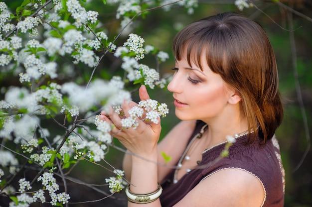 La bella donna sta odorando i fiori bianchi nel parco di primavera