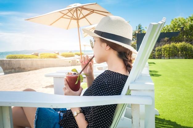 La bella donna sta rilassando sulla spiaggia, sotto l'ombrello