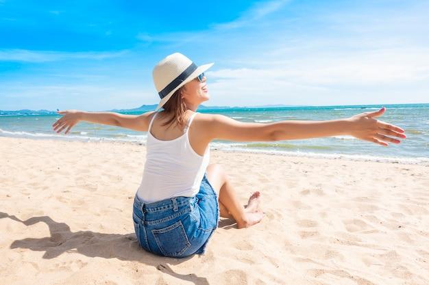 La bella donna sta sedendosi sulla spiaggia