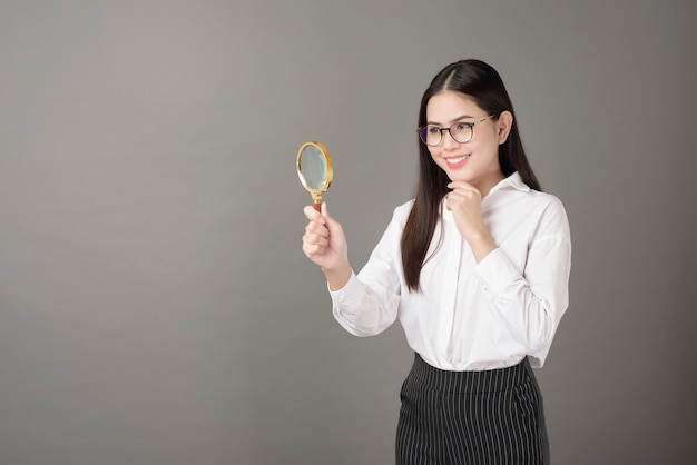 La bella donna sta tenendo la lente d'ingrandimento