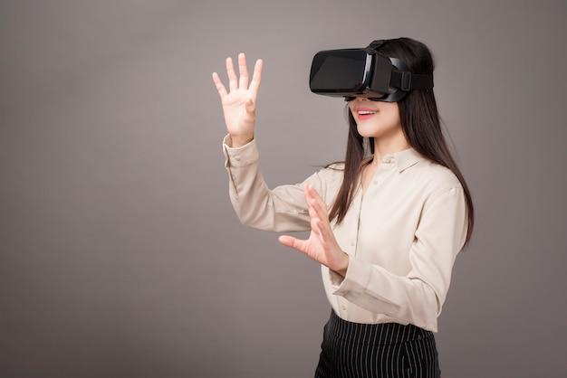 La bella donna sta usando la realtà virtuale su gray