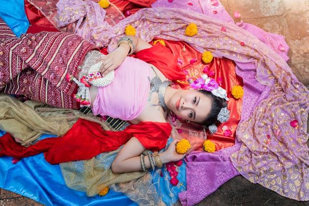 La bella donna tailandese che indossa i vestiti tradizionali tailandesi si riposa su seta