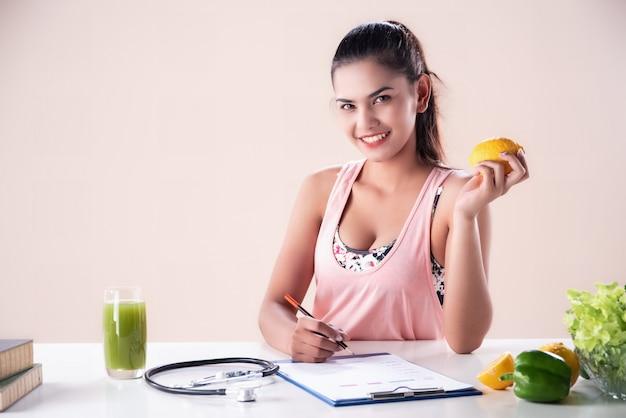 La bella donna tiene la frutta arancione nella mano sinistra, scrive sulla carta del piano di dieta con la mano destra, stethescope sfocato e succo verde messo sul tavolo,