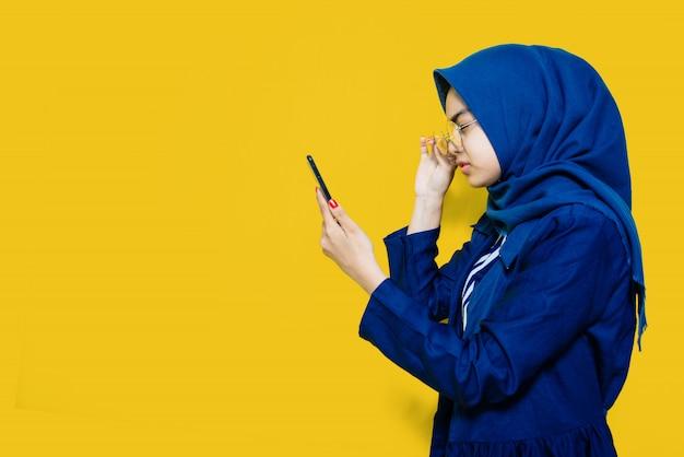 La bella donna vede il telefono con gli occhiali