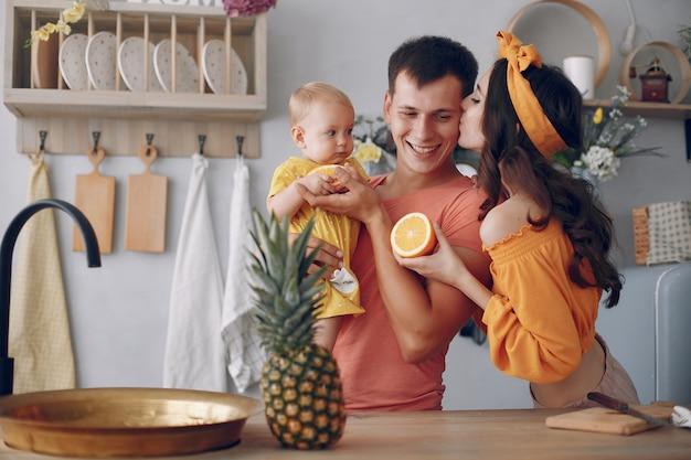 La bella famiglia prepara il cibo in una cucina