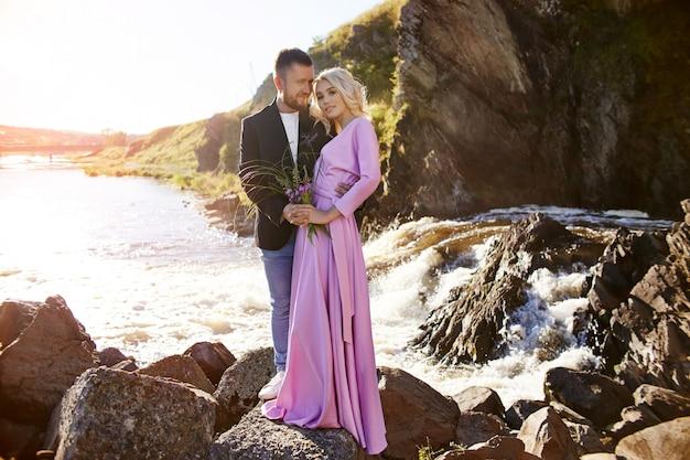 La bella giovane coppia abbraccia e distoglie lo sguardo e si gode un appuntamento romantico sul fiume