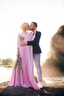 La bella giovane coppia abbraccia e distoglie lo sguardo e si gode un appuntamento romantico sul fiume.