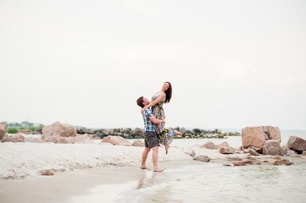 La bella giovane coppia cammina sul mare