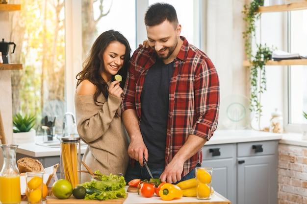 La bella giovane coppia felice sorridente sta parlando e sorridendo mentre cucinava l'alimento sano in cucina a casa.