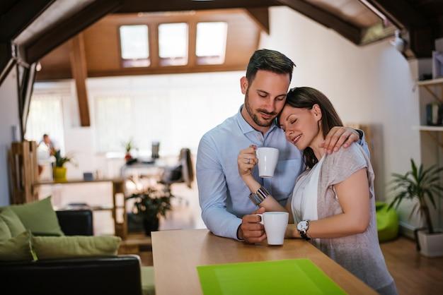 La bella giovane coppia sta abbracciando e sorridendo mentre beveva il tè in cucina a casa.